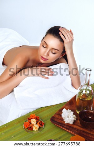 Spa-Day of Beautiful Woman on White and Bamboo at Salon - stock photo