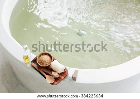 Spa decoration, natural organic products on a bathtube. Loofah, towel and frangipani flower, top view - stock photo