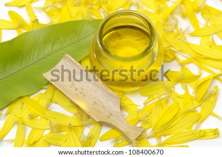 spa essential- bottle of massage oil and green leaf with yellow flower peals - stock photo