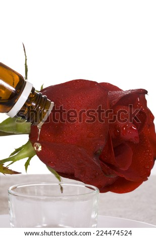 Spa essential oil dripping from the bottle and red rose - stock photo