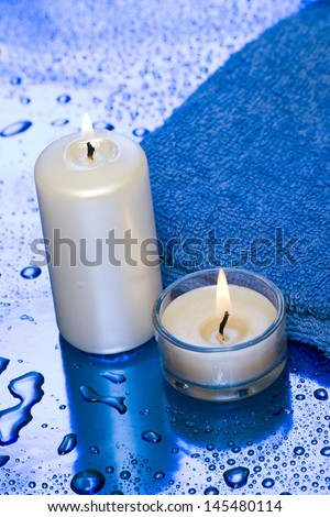 spa essentials, candles and towel on blue background  - stock photo