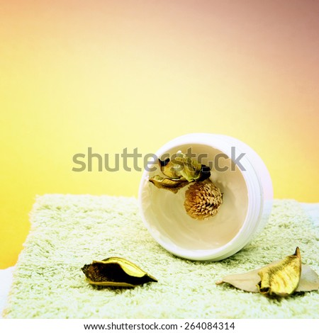 Spa essentials (cream, white towel and flowers) isolated on yellow - stock photo