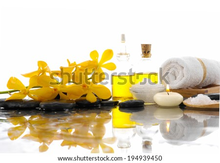Spa feeling with Orchid and burn candles ,black stones, oil , on wet background - stock photo