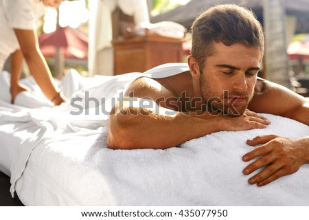 Spa For Man. Beautiful Healthy Happy Male Model Relaxing At Day Spa Beauty Salon. Handsome Guy Enjoying Summer Body Relaxation Treatment, Lying On Relax Massage Table Outdoors. Health Care Concept - stock photo