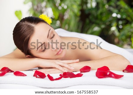 Spa girl. Attractive young woman looking at camera and smiling while lying on massage table