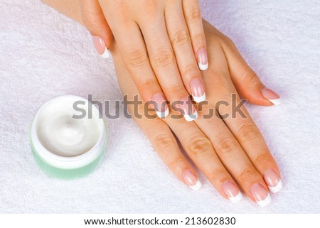 Spa hands with perfect french manicure near  jar of cream