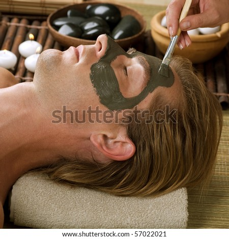 Spa.Handsome Man with a Mud Mask on his Face - stock photo