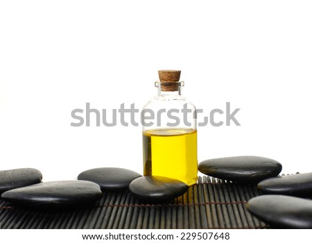 spa, health and beauty concept - closeup of essential oil, massage stones on mat - stock photo