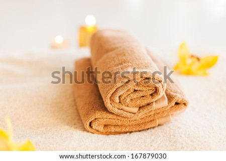 spa, health and beauty concept - closeup of towels, flowers and candles - stock photo