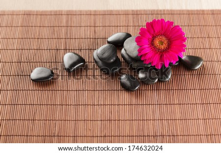 spa, heath and beauty concept - massage stones with flower on mat - stock photo