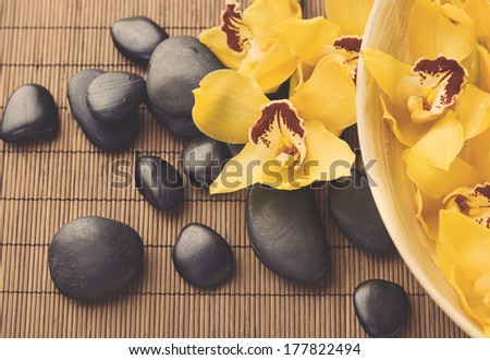 spa, heath and beauty concept - massage stones with orchid flowers on mat - stock photo