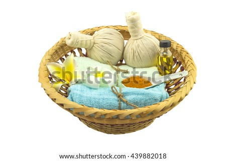 Spa herbal compressing ball , white frangipani flower , turmeric powder in white spoon massage oil and blue fabric  on bamboo basket isolate on white background.Saved with clipping path. - stock photo