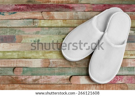 Spa, hotel - home slippers close on color planks wooden background with space for text - stock photo