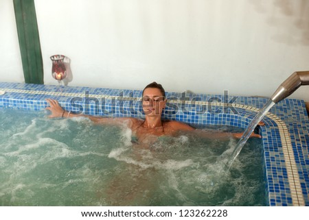 spa hydrotherapy woman waterfall swimming pool water - stock photo