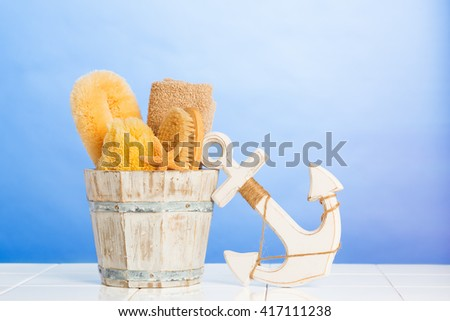 Spa items on fresh blue background with wooden anchor decoration - stock photo