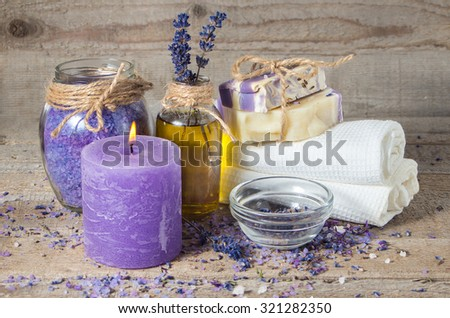 Spa lavender concept. Lavender oil, lavender flowers, handmade soap  and bath towels, sea salt and a burning aromatherapy candle. - stock photo
