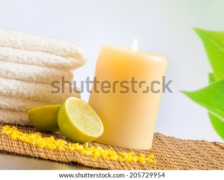 Spa massage border background with towel stacked and lime with leaves in background - stock photo