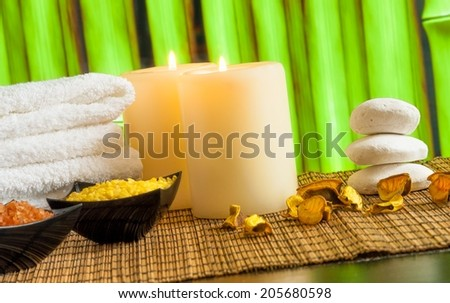Spa massage border background with towel stacked, candles and sea salt on bamboo background - stock photo