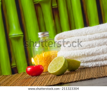Spa massage border background with towel stacked red candle and lime on bamboo background - stock photo