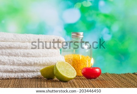 Spa massage border background with towel stacked,red candle and lime on green bokeh background - stock photo