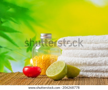 Spa massage border background with towel stacked,red candle and lime on green natural background - stock photo