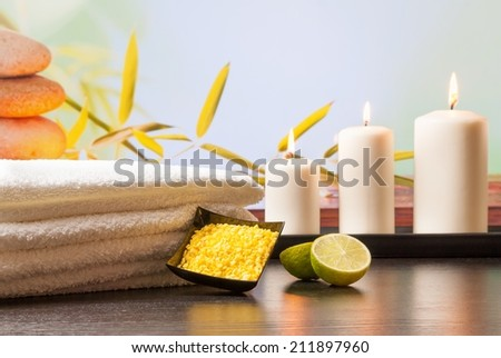 Spa massage border background with towel stacked sea salt candles and lime on natural background - stock photo