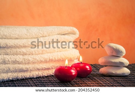 Spa massage border background with towel stacked stone and red candles on bamboo table - stock photo