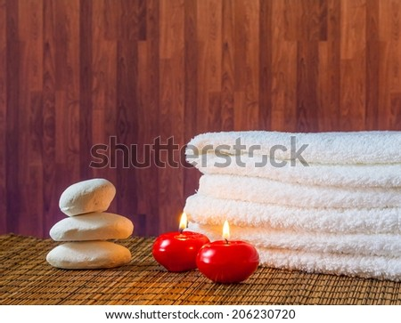 Spa massage border background with towel stacked stone and red candles on wood background warm atmosphere - stock photo
