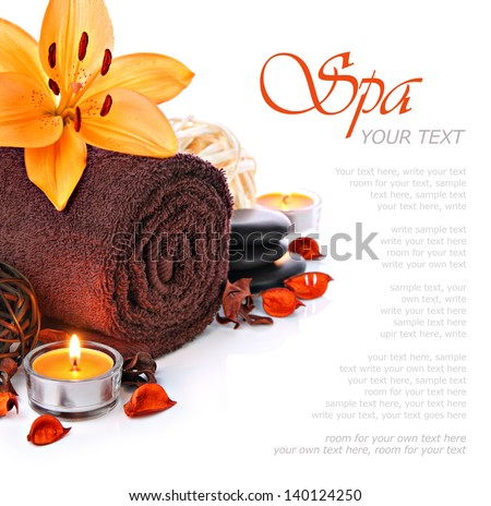 Spa massage border with a fluffy brown towel, candlelight and a orange lily flower - stock photo