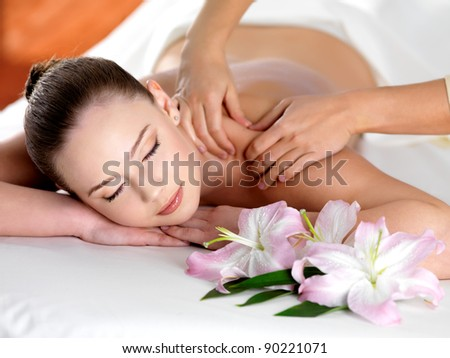 Spa massage on a shoulder for young beautiful woman in  beauty salon - indoors - stock photo