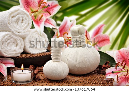 Spa massage setting with rolled towels and lily flowers  - stock photo