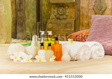 Spa massage setting with rolled towels and plumeria flowers - stock photo
