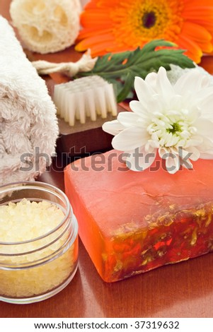 spa objects with towel sea salt soap brush and flower - stock photo