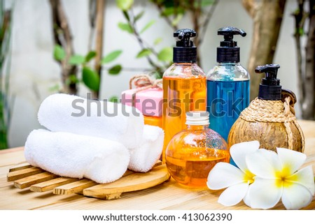 Spa oils in bottles on wooden table and nature background. - stock photo