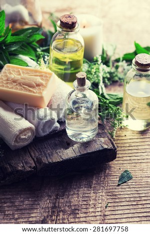 Spa or wellness setting. Essential aroma oil, towels, soap on aged  wooden background. Selective focus.  Toned image. - stock photo