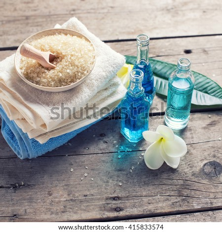 Spa or wellness setting in blue, yellow and white colors. Bottles with essential aroma oil, towels, sea salt  on  aged wooden background. Selective focus. Square image. Toned image. - stock photo