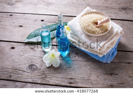Spa or wellness setting in blue, yellow and white colors. Bottles with essential aroma oil, towels, sea salt  on  aged wooden background. Selective focus. - stock photo