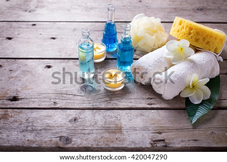 Spa or wellness setting in blue, yellow and white colors. Bottles with essential aroma oil, towels,  candles and wisps  on wooden background. Selective focus. Place for text.  - stock photo