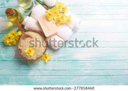 Spa or wellness setting. Natural sea salt in  wooden bow, organic soap, aroma oil, towels and yellow flowers  in ray of light on turquoise painted wooden background. Selective focus. Place for text.  - stock photo