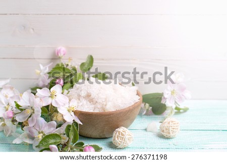 Spa or wellness setting. Sea salt in bowl and apple blossom in ray of light on turquoise wooden background against white wall. Selective focus is on salt.