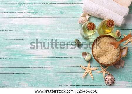 Spa or wellness setting. Sea salt in bowl, aroma oil, towels and sea objects  on turquoise painted wooden planks. Selective focus. Place for text.
