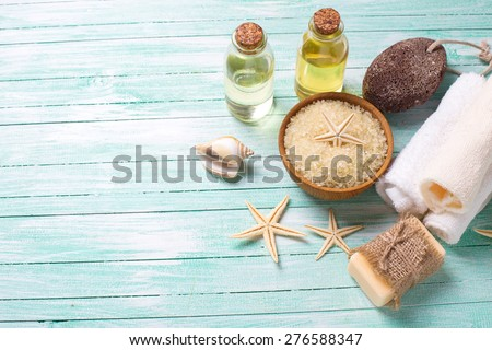 Spa or wellness setting. Sea salt in bowl, soap, aroma oil, pumice, towels and sea objects  on turquoise painted wooden planks. Selective focus is on sea salt.