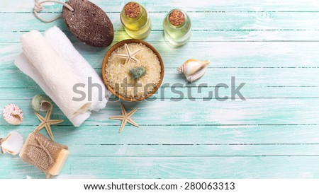 Spa or wellness setting. Sea salt in bowl, soap, aroma oil, pumice, towels and sea objects  on turquoise painted wooden planks. Selective focus. Place for text. Toned image.