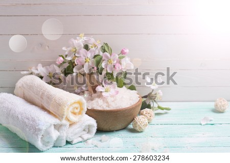 Spa or wellness setting. Sea salt in bowl, towels and apple blossom  in ray of light on turquoise wooden background against white wall. Selective focus is on towels and salt. Place for text. - stock photo