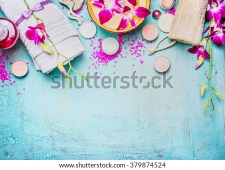 Spa or wellness setting with pink purple orchid flowers , bowl of water, towel, cream , sea salt and nature sponge on turquoise blue background, top view, place for text. Body care concept - stock photo