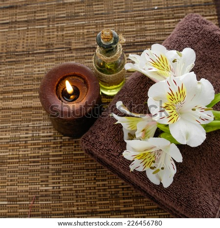 spa orchid flower with candle oil on mat