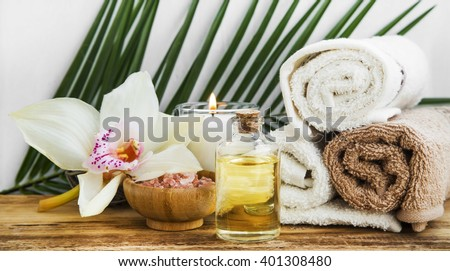 Spa orchid still life setting with body oil, towels and salt