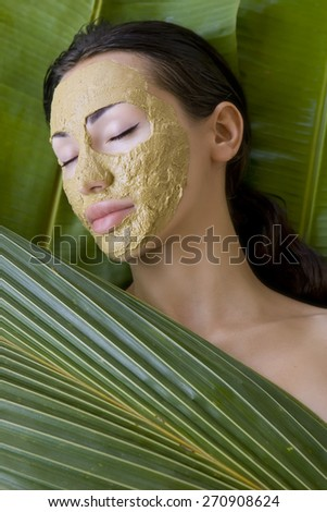 Spa Outdoor, Beautiful young woman lying with natural clay herbal facial mask, beauty spa, skin care and wellness in Thailand - stock photo