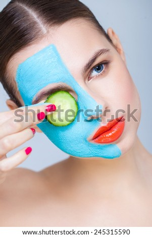 Spa portrait with a clay mask and cucumber