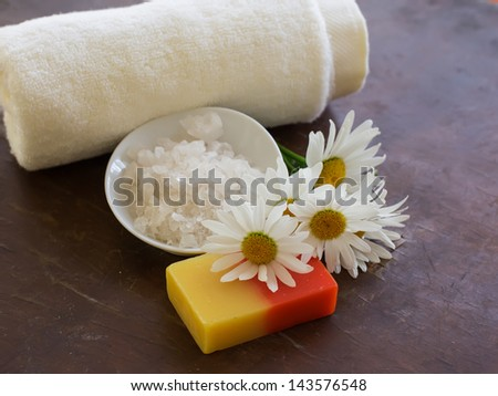 Spa products on wooden background. Sea salt, soap with natural components chamomile. Selective focus.